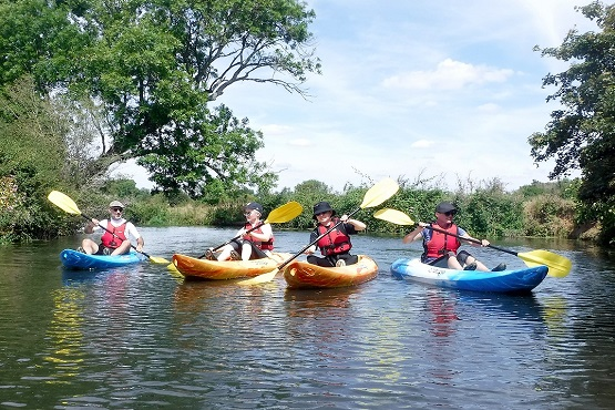 Group kayaking on a river with Hatt Adventures