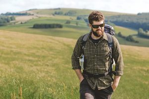 Man with beard, sunglasses and rucksack walking in the country