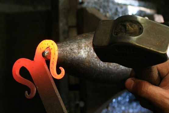 Hot metal being made into a bespoke piece by a blacksmith at Chalk Pit Forge