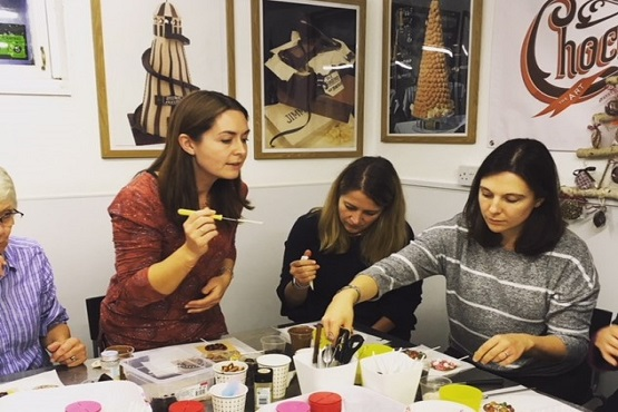 A chocolatician tasting homemade chocolate goods being made at a workshop