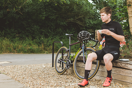 A cyclist stopping off for a coffee on the Downs Link route in West Sussex