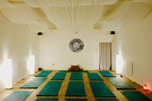 Yoga room with green yoga mats and tranquil lighting and decor