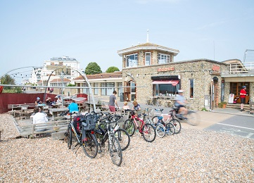 Bikes lined up in front of a cafe on the pebble beach in Worthing