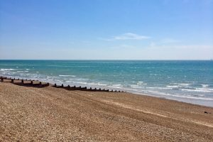 Goring Gap Beach with pebbles, groynes and the blue sea