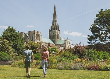 Chichester Cathedral with couple walking in the gardens in spring