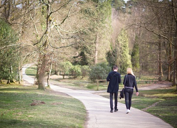 Couple walking along a path in a park in Crawley