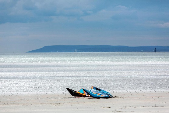 West Wittering Beach scape with two windsurfing boards in front of the sea and headland in distance