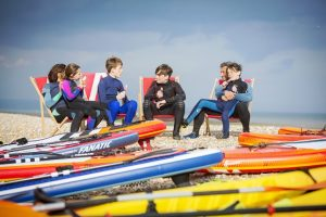 Group of children on deck chairs eating ice lollies after paddleboarding