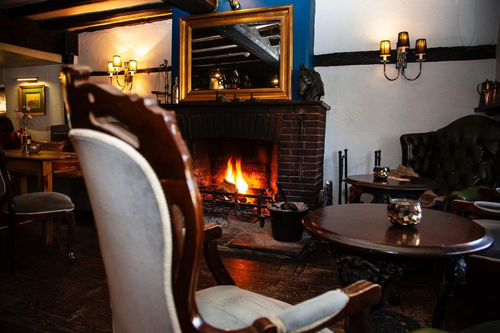 Armchair and cosy fireplace at The Queens Head in West Chiltington