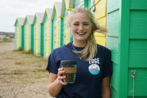 Smiling staff member from Edge by the Sea independent coffee shop infront of green and yellow beach huts in Littlehampton, Sussex
