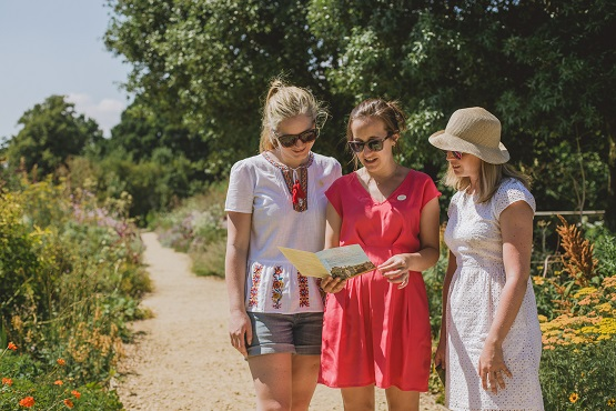 Three women reading map directions in Parham House gardens