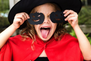 Young girl dressed in halloween costume holding cut out pumpkins to face
