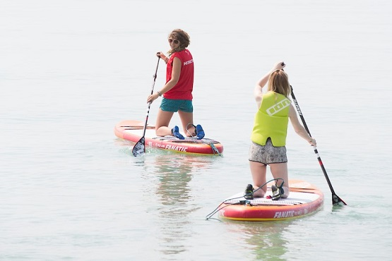 Paddle board instructor and student in the water