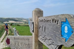 South Downs Way sign post with cyclists in the background