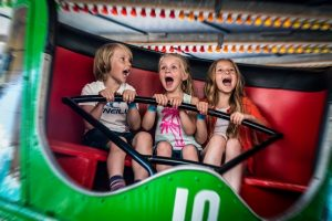Three young children on the waltzer at Harbour Park