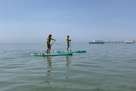 Two paddleboarders in the water by Worthing Pier