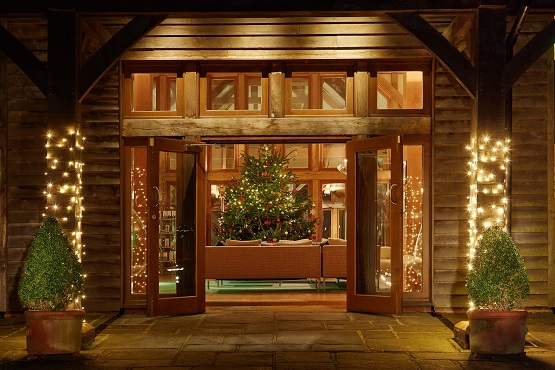 Wooden Christmas barn decorated with trees and lights with open glass doors