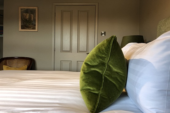 Green pillow on double bed at the East Beach Guest House in Littlehampton