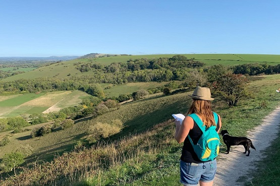 A woman and dog overlooking the South Downs in summer