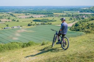 Male cyclist sitting back on bike overlooking the South Downs