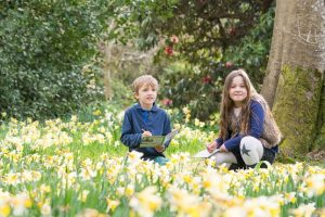 Children playing in a field of daffodils for Easter at Borde Hill