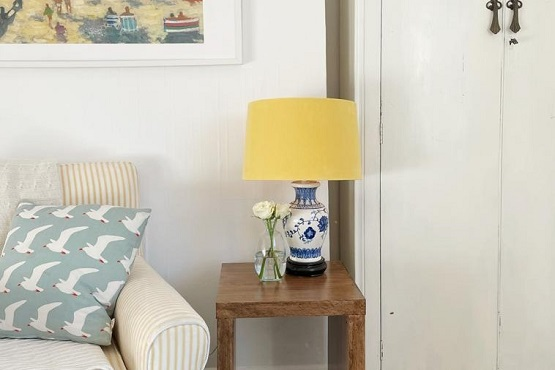 Yellow lamp positioned on top of a wooden side table in a living area