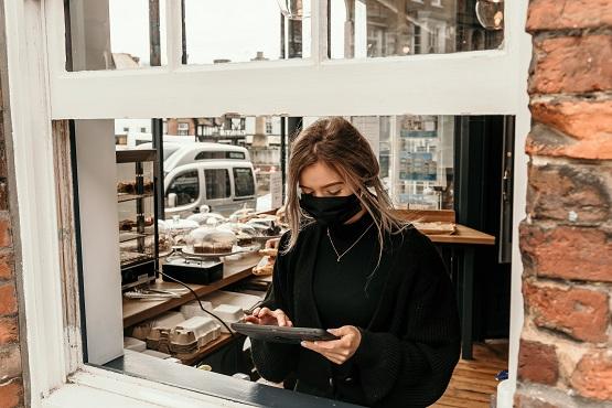 Staff behind coffee shop window wearing a mask taking an order