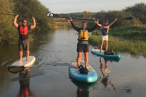 Three paddleboarders standing on their paddleboards holding the ore above their head