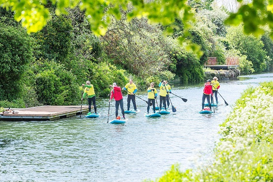 A group of stand up paddleboarders travelling down a river