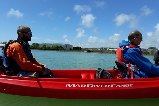 Guided kayak tour with two men sitting in red kayak