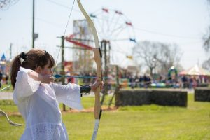 Young girl holding bow and arrow at a fun fair