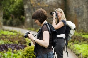 Visitors taking photographs in the garden at Buckland Abbey, Devon.