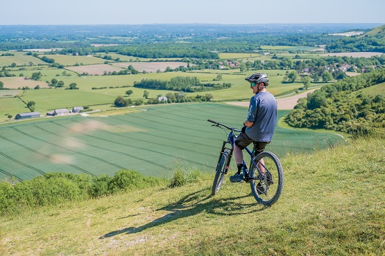 Cyclist sitting on his bike overlooking the South Downs